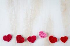 Связанные красные сердца на белой деревянной предпосылке Стоковая Фотография RF