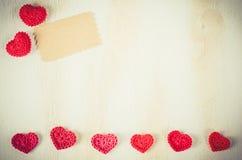 Связанные красные сердца на винтажной деревянной предпосылке Стоковая Фотография