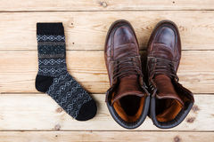 Связанные носки и кожаные ботинки на деревянной предпосылке Стоковые Изображения