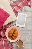 Связанные подушки и шотландка, eBook, круассаны и кофе на lig Стоковое фото RF