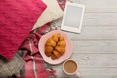 Связанные подушки и шотландка, eBook, круассаны и кофе на lig Стоковые Изображения RF