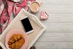 Связанные подушки и шотландка, smartphone, круассаны и кофе дальше Стоковое Изображение RF