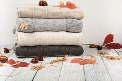 Связанные свитеры шерстей Куча связанной зимы, осени одевает на деревянной предпосылке, свитерах, knitwear, космосе для текста Стоковые Изображения
