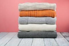 Связанные свитеры шерстей Куча связанной зимы одевает на красной деревянной предпосылке, свитерах, knitwear, космосе для текста Стоковая Фотография RF