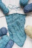 Связанные шарф и пасма шерстей на деревянном столе Стоковая Фотография RF