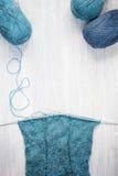 Связанные шарф и пасма шерстей на деревянном столе Стоковые Фотографии RF