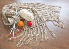 Связанный шарф, шарики пряжи и вязать иглы на деревянной предпосылке Стоковая Фотография RF