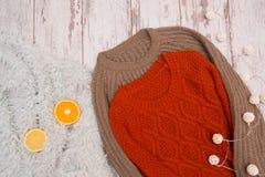 2 связанных свитера на деревянной предпосылке Цитрус, меха и гирлянда модная концепция Стоковая Фотография