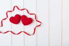 2 связанных сердца на белой деревянной предпосылке Карточки дня валентинок Стоковое Фото