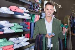 Связи клиента рассматривая в мужском магазине одежды Стоковые Фото