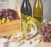 Связки винограда, рюмка, бутылки и пробочки на деревянной предпосылке Стоковое Изображение RF