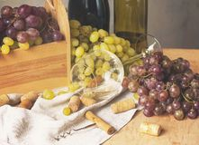 Связки винограда, рюмка, бутылки и пробочки на деревянной предпосылке Стоковые Изображения