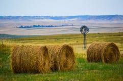 Связки сена в поле с ветрянкой Стоковое Изображение