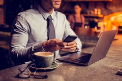Связь бизнесмена нося сидя в баре и отправляя SMS друге стоковое фото rf