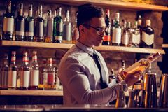 Связь бизнесмена нося смотря бутылку вискиа в его ресторане стоковые изображения rf