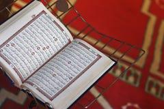 Святейшая книга Quran на красном исламском половике   Стоковое фото RF