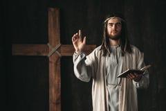 Святой Иисус Христос моля с библейским в руках стоковые фото