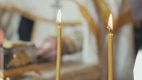 2 святых свечи, священник декламируя молитву от библии на запачканной предпосылке акции видеоматериалы