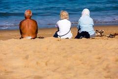 Свят-Джин de Luze, Франция - SEPT. 28, 2016: семья сидя на пляжных полотенцах в песке 3 люд, один человек и 2 женщины они Стоковая Фотография