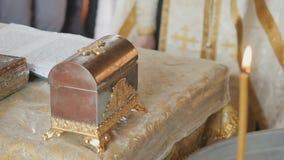 Священник в сутане стоит около таблицы при библия, горя свечу на переднем плане акции видеоматериалы