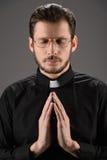 Священник моля к богу. Портрет священника моля пока стоящ стоковое изображение