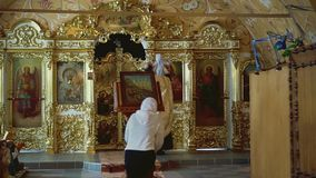 Священник носит ребенка к алтару акции видеоматериалы