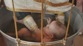 Священник окунул младенца в воде в шрифте во время ритуала крещения акции видеоматериалы