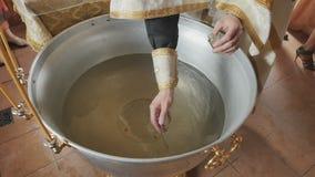 Священник пересекает воду в шрифте с щеткой перед церемонией крещения сток-видео
