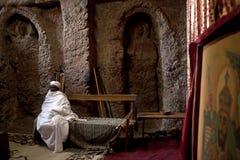 Священник сидеть в монолитовой церков Стоковая Фотография