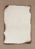 Сгорели бумажная карточка над мешковиной стоковое изображение rf