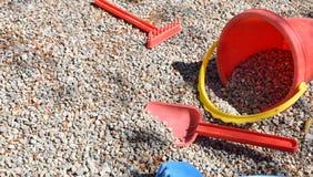 Сгребите ребенка лопаткоулавливателя и ведра на гравии спортивной площадки Стоковое Изображение