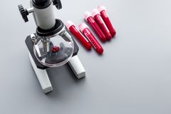 Сделайте анализ крови в лаборатории аналитиков Пробы крови в пробирках приближают к микроскопу на сером экземпляре взгляд сверху  Стоковое Изображение