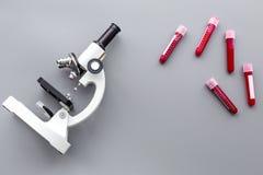 Сделайте анализ крови в лаборатории аналитиков Пробы крови в пробирках приближают к микроскопу на сером экземпляре взгляд сверху  Стоковые Фотографии RF