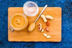 Сделайте арахисовое масло Затир в стеклянном опарнике на столе вырезывания около арахиса на голубом взгляд сверху предпосылки Стоковые Изображения
