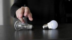 Сделайте выбор между старой лампой накаливания и новой энергосберегающей электрической лампочкой СИД Взгляд со стороны сток-видео