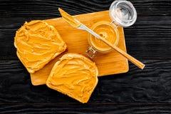 Сделайте здравицу с затиром гайки 2 toastes, нож и стекла раздражают с затиром гайки на черной деревянной предпосылке Стоковые Изображения RF