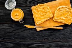 Сделайте здравицу с затиром гайки 2 toastes, нож и стекла раздражают с затиром гайки на черном деревянном космосе предпосылки для Стоковые Изображения RF