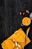 Сделайте здравицу с затиром гайки 2 toastes, нож и стекла раздражают с затиром гайки на черном деревянном космосе предпосылки для Стоковые Фото