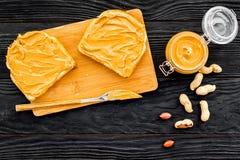 Сделайте здравицу с затиром гайки 2 toastes, нож и стекла раздражают с затиром гайки на черной деревянной предпосылке Стоковые Фото