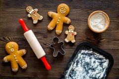 Сделайте печенье пряника на Новый Год 2018 Человек пряника, вращающая ось, мука на темном деревянном взгляд сверху предпосылки Стоковое Фото