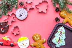 Сделайте печенья пряника на Новый Год дома Хлебопекарня и резцы на розовом copyspace взгляд сверху предпосылки Стоковое Фото