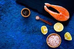 Сделайте солёных рыб Сырцовый salmon стейк на разделочной доске около соли моря, перца, кусков лимона на голубом взгляд сверху пр Стоковые Изображения RF