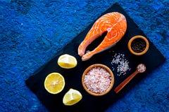 Сделайте солёных рыб Сырцовый salmon стейк на разделочной доске около соли моря, перца, кусков лимона на голубом взгляд сверху пр Стоковое Фото
