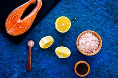 Сделайте солёных рыб Сырцовый salmon стейк на разделочной доске около соли моря, перца, кусков лимона на голубом взгляд сверху пр Стоковая Фотография