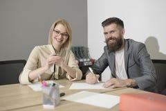 Сделанный колодец, усмехающся женские и мужские коллеги компании сидит на столе в офисе Счастливые деловые партнеры празднуя подп Стоковое Фото