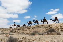 Сделанный силуэтов металла идя каравана людей, ослов и верблюдов около руин города Avdat Nabataean, в Ju стоковые фото