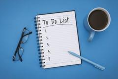 Сделать список на тетради над пастельной голубой предпосылкой стоковое фото rf