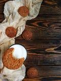 сдержанное печенье овсяной каши с стеклом молока на деревянном столе и бегуне бежа Стоковое Изображение