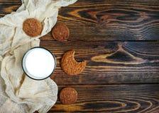 сдержанное печенье овсяной каши с стеклом молока на деревянном столе и бегуне бежа Стоковая Фотография RF