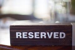 Сдержанно деревянная плита карточки на таблице с расплывчатой предпосылкой Место ресервирования на ресторане - отдых, люди и обсл стоковое изображение rf